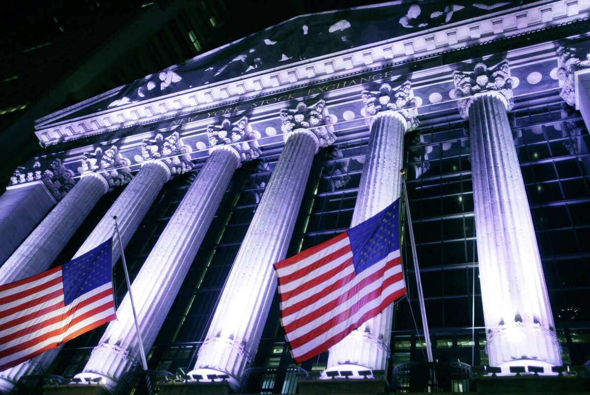 In this Wednesday, Oct. 8, 2014 photo, American flags fly in front of the New York Stock Exchange. U.S. stocks were barely higher in early trading Monday, Dec. 29, 2014, as Wall Street winds down the year in this holiday-shortened week.