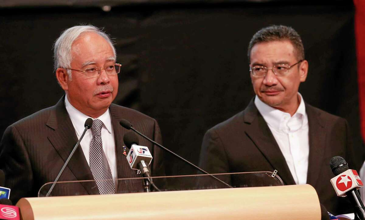Malaysia's Prime Minister Najib Razak , left, and acting transport minister Hishammuddin Hussein speak during the press conference for the missing Malaysia Airlines jet, MH370, at Putra World Trade Centre (PWTC) in Kuala Lumpur, Malaysia, Monday, March 24, 2014.
