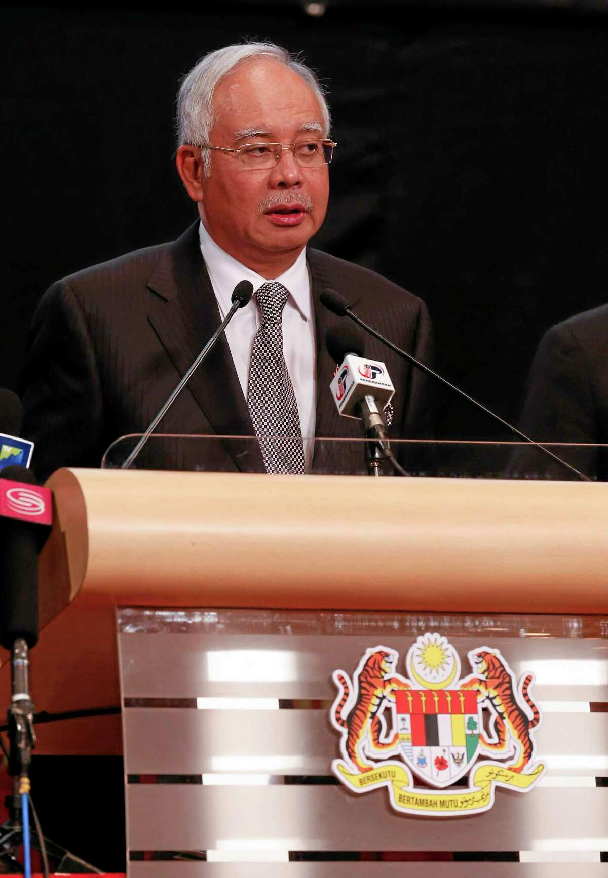 Malaysia's Prime Minister Najib Razak speaks during the press conference for the missing Malaysia Airline, MH370 at Putra World Trade Centre (PWTC) in Kuala Lumpur, Malaysia, Monday, March 24, 2014. Razak says new data show missing plane plunged into southern Indian Ocean. (AP Photo/Vincent Thian)