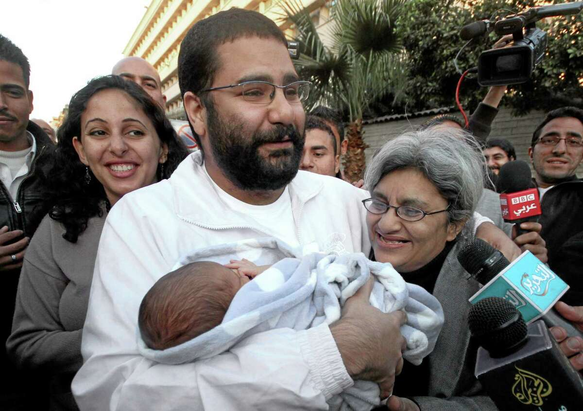 FILE - In this Sunday, Dec. 25, 2011 file photo, Egyptian prominent blogger Alaa Abdel-Fattah, center, hugs his recently born son, Khaled, his mother Laila Soueif, and his sister Ahdaf Soueif, left, after his release, in Cairo, Egypt. An Egyptian court has ordered Abdel-Fattah who has spent nearly four months in jail to be released on bail. Egyptian authorities detained Abdel-Fattah, a leading figure in the 2011 uprising against Hosni Mubarak, in November, and charged him with organizing a protest without permission and assaulting police. (AP Photo/Amr Hafez, File)