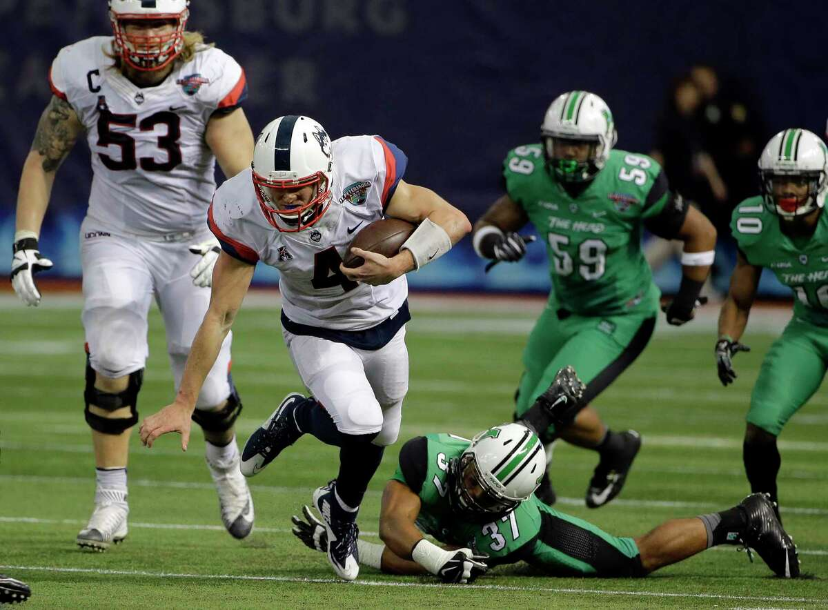 UConn quarterback Bryant Shirreffs (4) is tripped up by Marshall safety Chase Hancock during the St. Petersburg Bowl on Saturday.