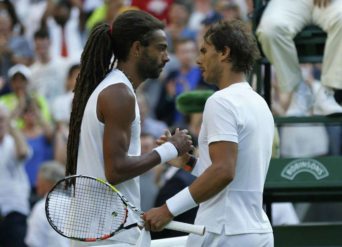 Dustin Brown, left, shakes hands at the net with Rafael Nadal after defeating him Thursday at the All England Lawn Tennis Championships in Wimbledon, London.