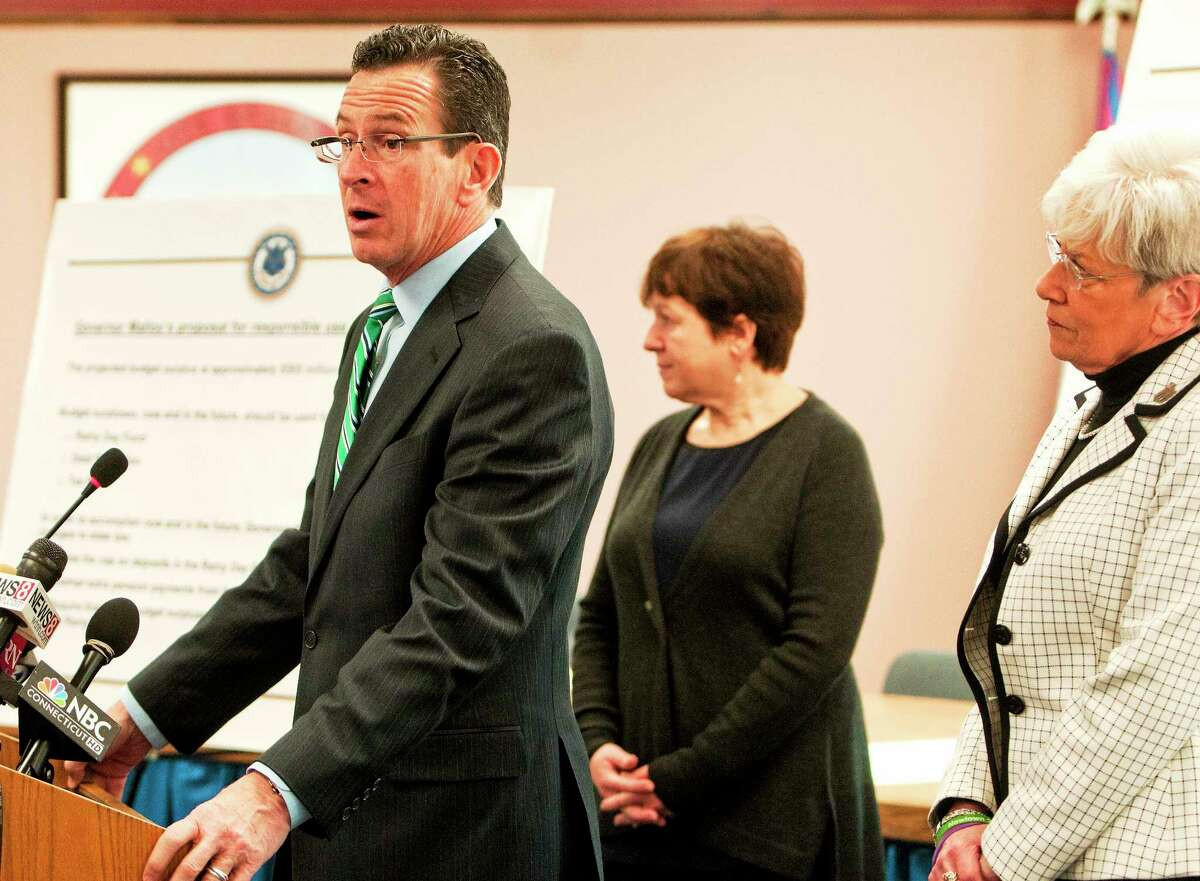 (Photo by Peter Hvizdak ó New Haven Register) ¬ Governor Dannel P. Malloy, with Derby Mayor Anita Duggato, center, and Lt. Governor Nancy Wyman, right, announces a three-point plan for the budget surplus during a press conference Thursday January 30, 2014 at Derby City Hall.