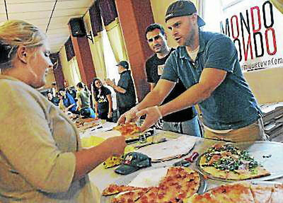 Catherine Avalone The Middletown Press Manager of Mondo's Pizza in Middletown Keith Vibert, at right and head chef Dave Noad serves up a slice of pizza.