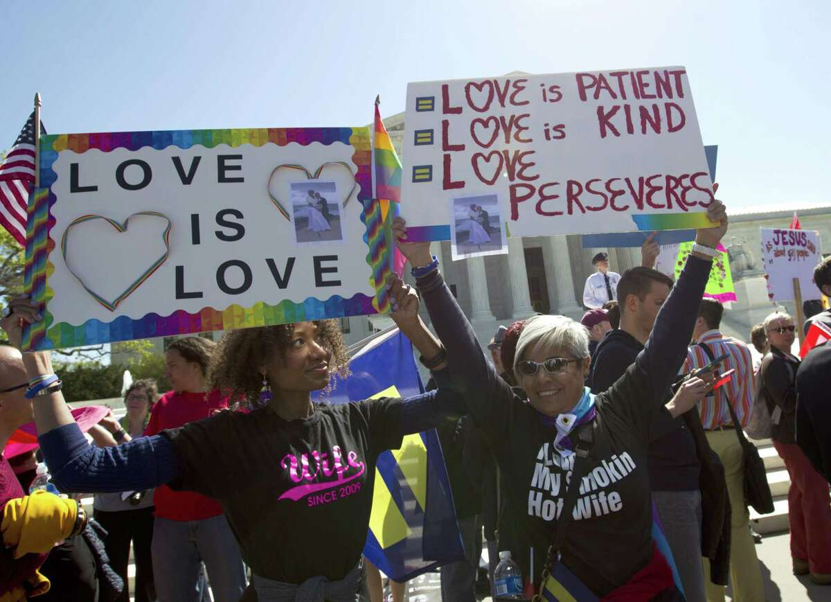 Ikeita Cantu, left, and her wife, Carmen Guzman, hold banners outside the Supreme Court in Washington, D.C., Tuesday.