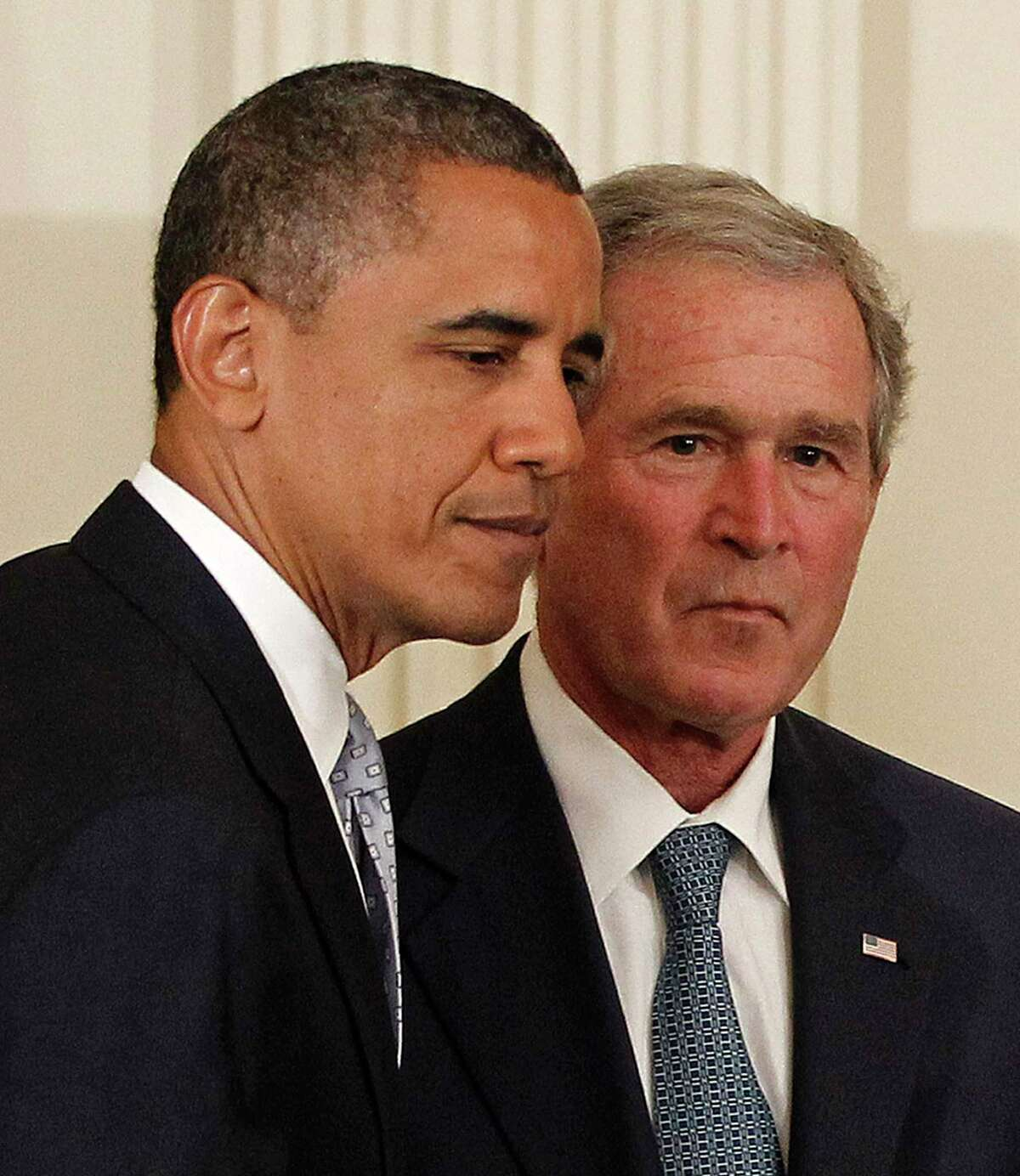 """FILE - In this Thursday, May 31, 2012, file photo, President Barack Obama and former President George W. Bush take part in a ceremony in the East Room of the White House in Washington, to unveil the Bush portrait. Taunted by Republicans to declare war on """"radical Islamic terrorism,"""" Democrats are turning to an unlikely ally: George W. Bush. Obama, under pressure to be more aggressive on terrorism, regularly cites his predecessor's refusal to demonize Muslims or play into the notion of a clash between Islam and the West. It's a striking endorsement from a president whose political rise was predicated on opposition to the Iraq war and Bush's hawkish approach in the Middle East."""