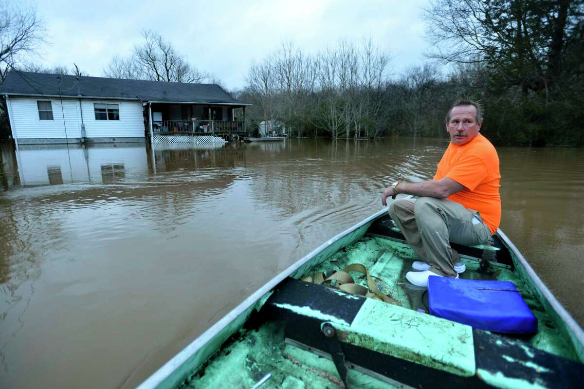 Wayne Horton steers his boat past his house on a flooded Clinton Street in Courtland, Ala. as he goes to check on neighbors Saturday, Dec. 26, 2015.