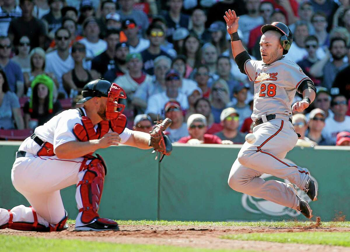 The Orioles' Steve Pearce, right, scores on an RBI single by Nelson Cruz in the seventh inning on Sunday.