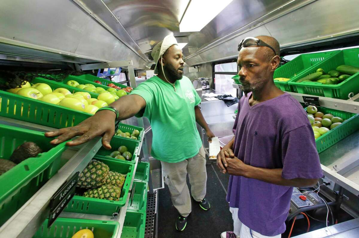 Fresh Stop employee Jamar Allen, left, helps Jock Riggins as he shops on the Fresh Stop bus, a mobile market, in Eatonville, Fla. The Fresh Stop brings fresh fruits and vegetables to communities with no supermarkets.
