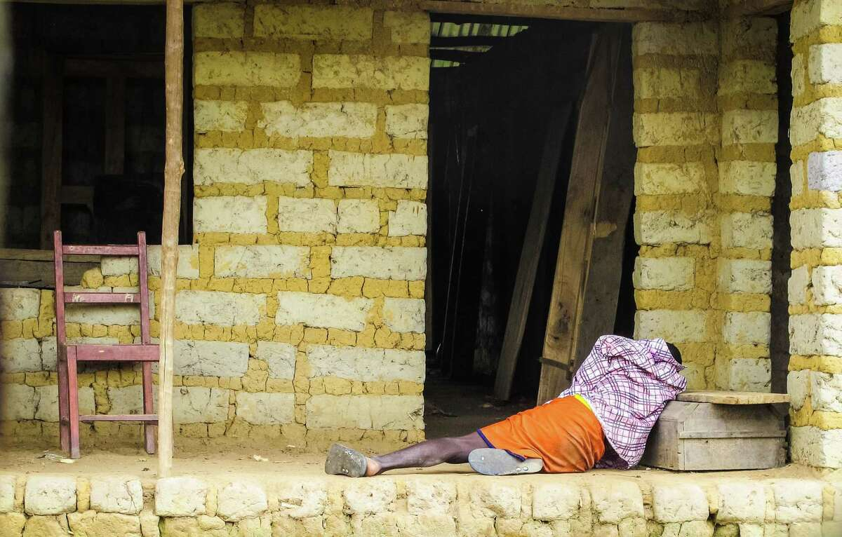 In this Tuesday, Oct. 21, 2014 photo, a man suffering from the Ebola virus lies on the floor outside a house in Port Loko Community, situated on the outskirts of Freetown, in Sierra Leone.