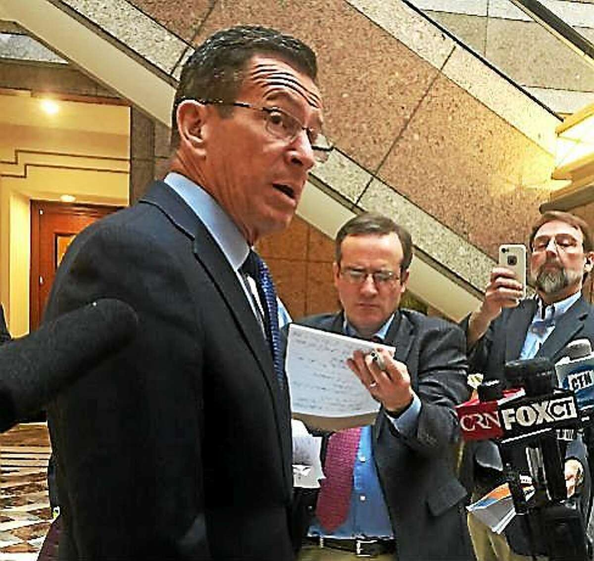 Gov. Dannel P. Malloy talks to reporters about his transportation plans.