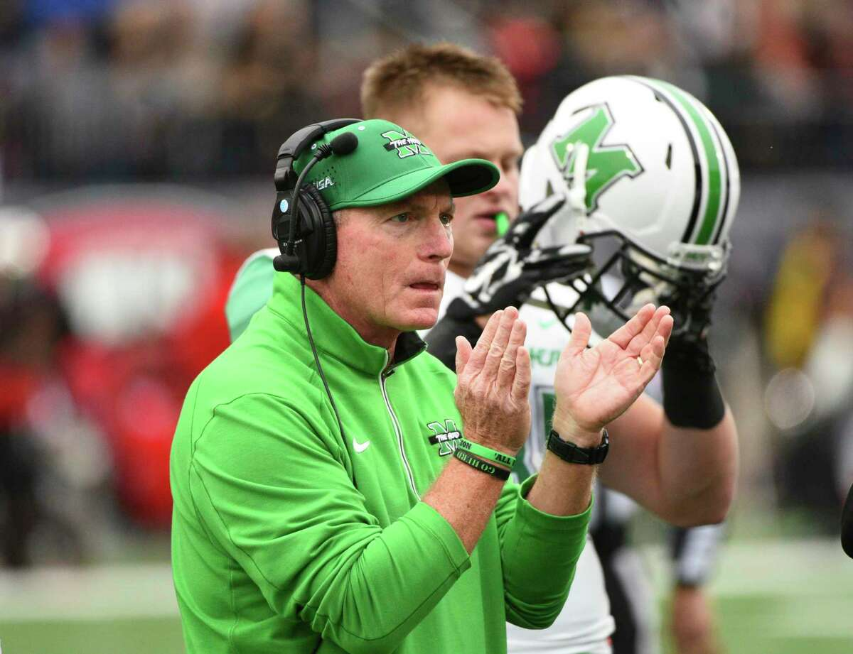 In this Nov. 27, 2015 photo, Marshall's Doc Holiday claps for his players during the first half of an NCAA college football game against Western Kentucky, in Bowling Green, Ky.