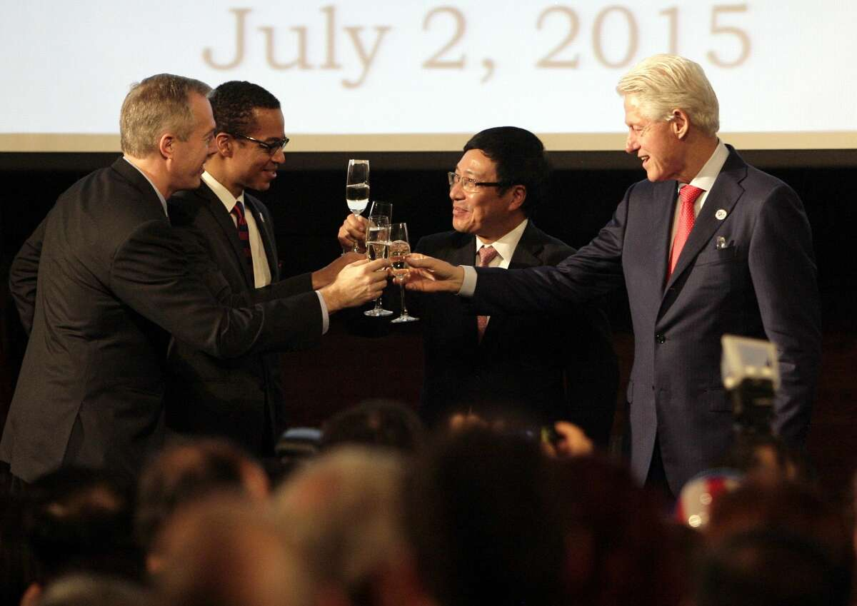 Former U.S. President Bill Clinton, right, Vietnamese Deputy Prime Minister and Foreign Minister Pham Binh MInh, second from right, Clayton Bond, spouse of U.S. Ambassador Ted Osius, third from right and U.S. Ambassador Ted Osius, far left, toast at an event celebrating 239th anniversary of the U.S. independence and 20th anniversary of normalization of relations between the U.S. and Vietnam on Hanoi, Vietnam on Thursday July 2, 2015. Clinton lifted the trade embargo against Vietnam in 1994 and normalized relations with the communist country a year later. (AP Photo/Tran Van Minh.)