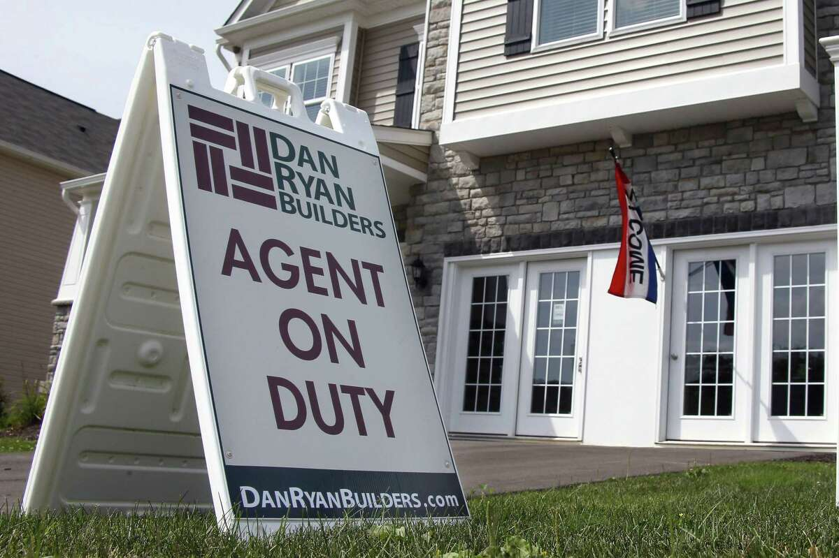 This Sept. 10, 2014 file photo shows signs welcoming visitors to a model home as construction is under way at a housing development in Zelienople, Pa.