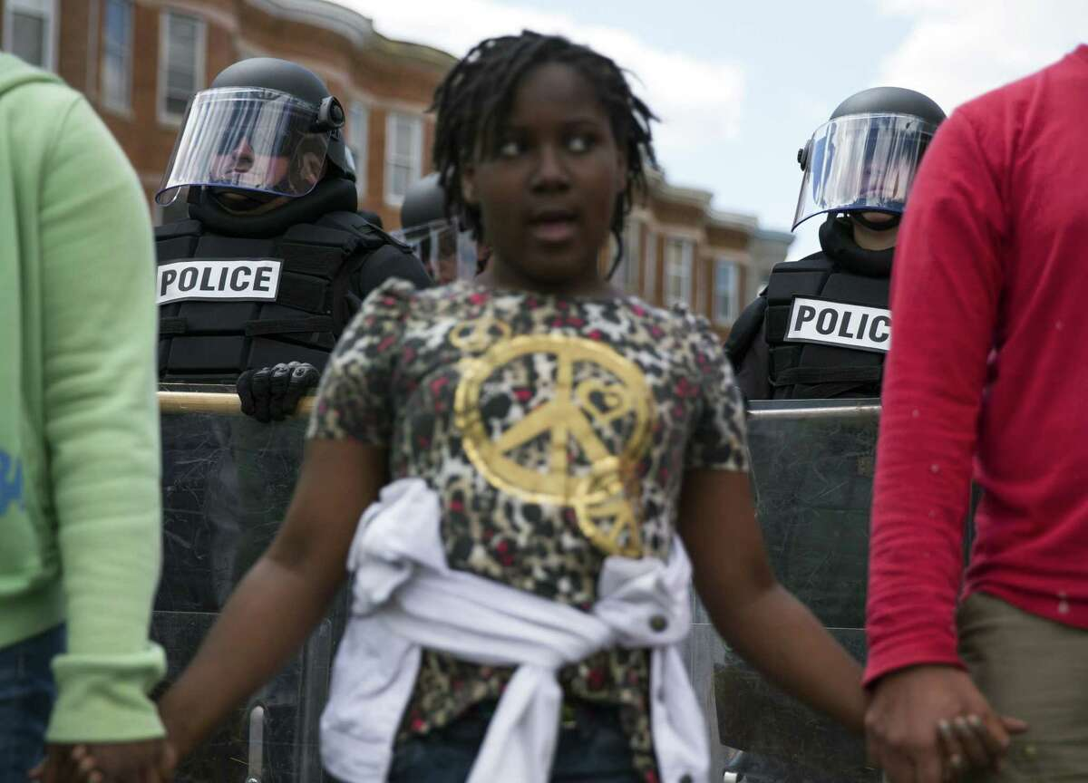 Police look on as demonstrators gather after an evening of riots following the funeral of Freddie Gray on Tuesday, April 28, 2015, in Baltimore. Gray died from spinal injuries about a week after he was arrested and transported in a Baltimore Police Department van.