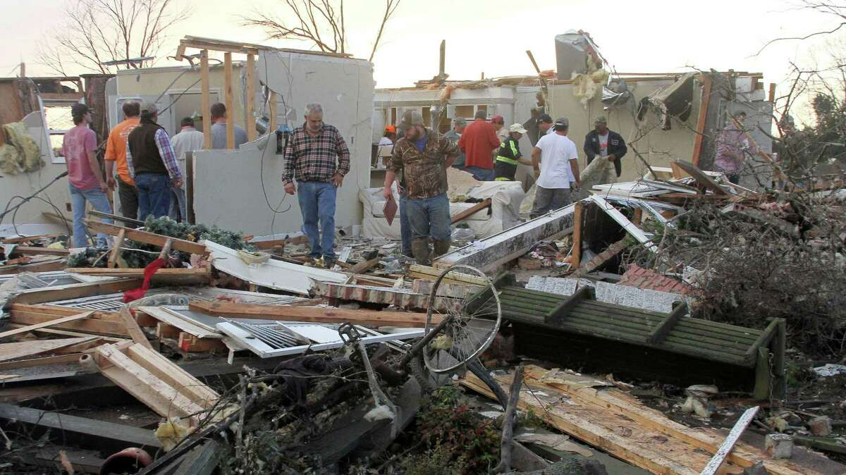 """People inspect a storm-damaged home in the Roundaway community near Clarksdale, Miss. on Dec. 23, 2015. A storm system forecasters called """"particularly dangerous"""" killed multiple people as it swept across the country Wednesday."""