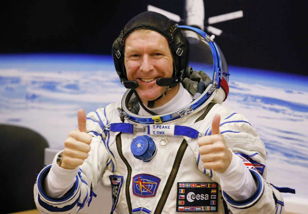 In this Dec. 15, 2015 photo, British astronaut Tim Peake, member of the main crew of the expedition to the International Space Station (ISS), gestures prior the launch of Soyuz TMA-19M space ship at the Russian leased Baikonur cosmodrome, Kazakhstan.