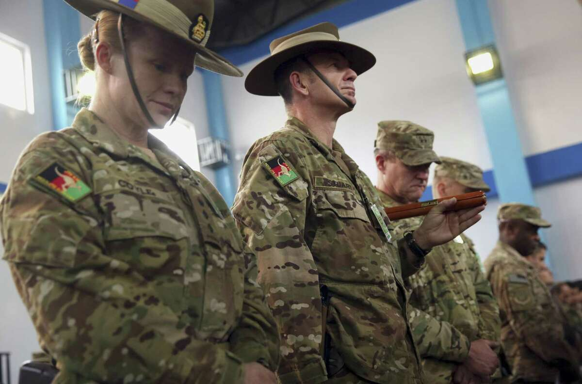 Soldiers for the International Security Assistance Force (ISAF) attend a ceremony at the ISAF headquarters in Kabul, Afghanistan, on Dec. 28, 2014.