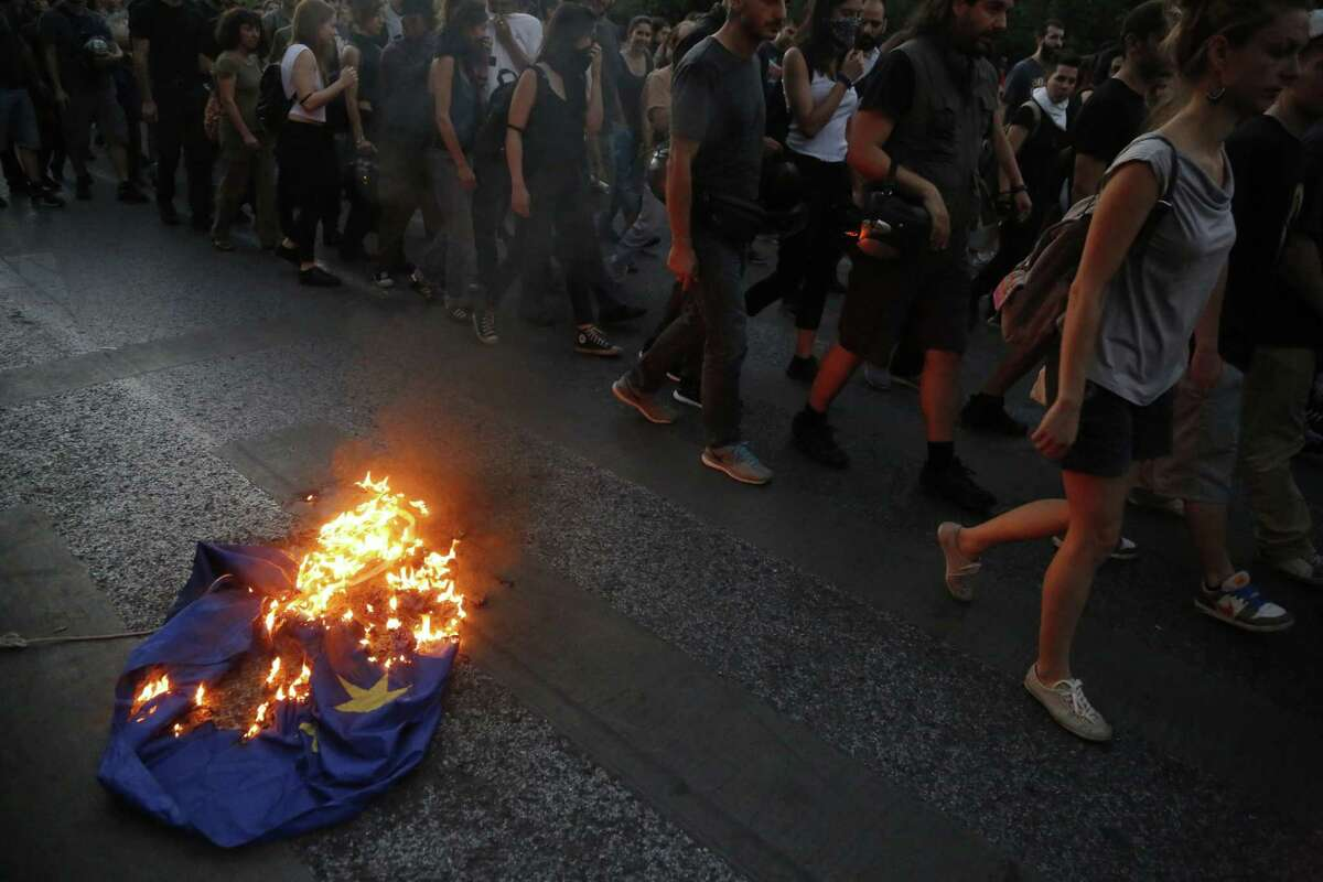 Demonstrators burn a European Union flag during a rally supporting the no vote for the upcoming referendum outside European Union office in Athens, Thursday, July 2, 2015. Greeks are now restricted to daily cash withdrawals of 60 euros, as the country heads to a crucial referendum Sunday that could decide whether the country falls out of the euro. (AP Photo/Petros Karadjias)