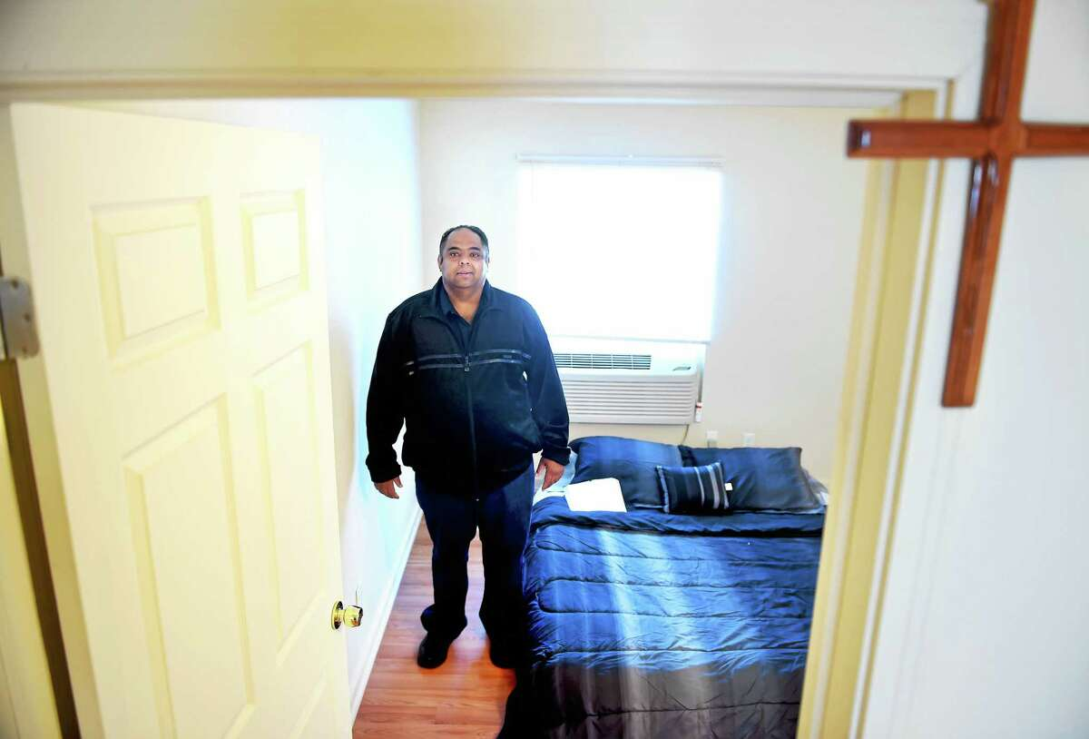 Joseph White, who was formerly homeless, keeps a Bible on his bed at his apartment in Hamden.
