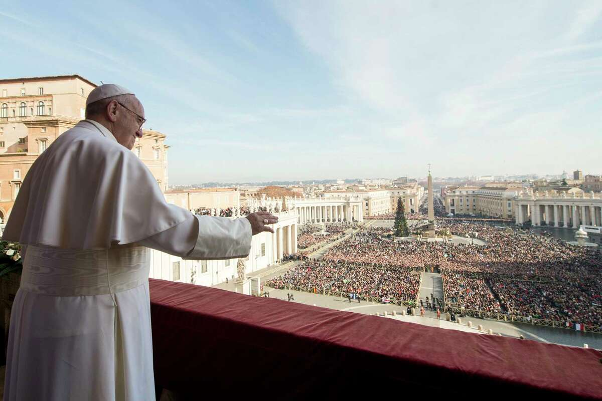 """Pope Francis delivers his """"Urbi et Orbi"""" (to the city and to the world) blessing from the central balcony of St. Peter's Basilica at the Vatican on Dec. 25, 2015."""