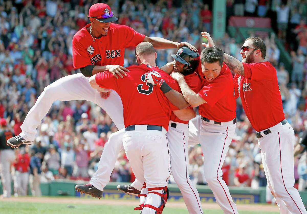 The Red Sox's Jonathan Herrera, center, celebrates his game-winning RBI single with teammates Xander Bogaerts, left, David Ross (3), Koji Uehara, second from right, and Mike Napoli, right, in the ninth inning of the first game of a doubleheader against the Baltimore Orioles on Saturday in Boston. The Red Sox won 3-2.