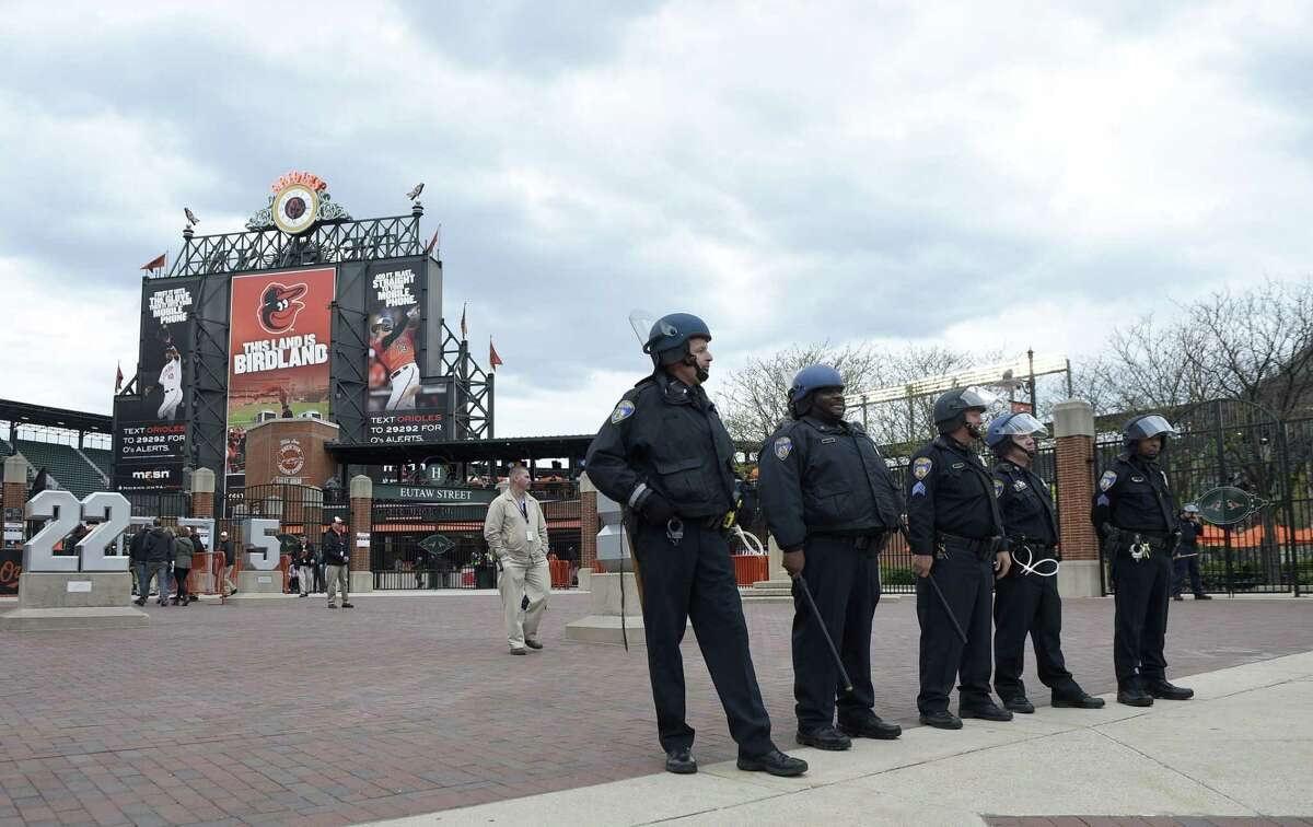 Baltimore police officers stand guard outside of Oriole Park at Camden Yards on Monday in Baltimore.