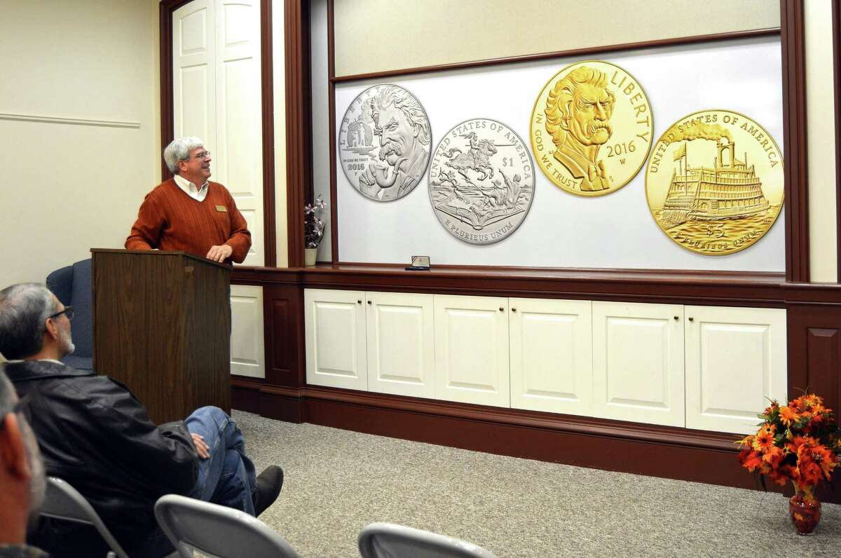 In this Nov. 30, 2015 photo, Henry Sweets, executive director of the Mark Twain Boyhood Home & Museum in Hannibal, Mo., unveils the design for commemorative gold and silver Mark Twain coins that will be sold starting next year.
