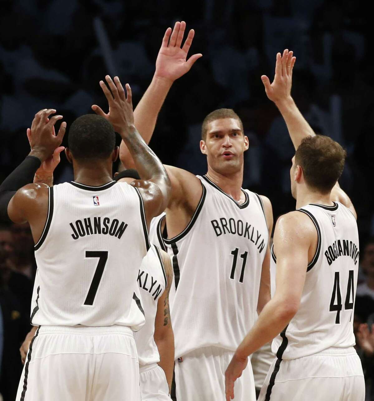 Nets center Brook Lopez (11) celebrates with Nets forward Joe Johnson (7) and guard Bojan Bogdanovic (44) Monday night.
