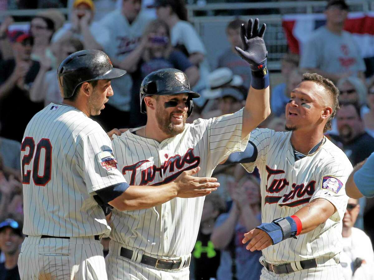 The Minnesota Twins' Chris Colabello, left, and Oswaldo Arcia, right, celebrate with Trevor Plouffe, center, after Plouffe grounded into a fielder's choice and Josh Willingham scored the winning run on a throwing error by New York Yankees catcher Francisco Cervelli during the eleventh inning of Saturday's game in Minneapolis.