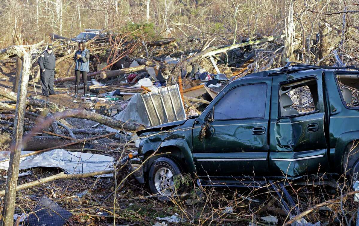 A vehicle sits among debris Thursday in an area near Linden, Tenn. Several people were killed in Mississippi, Tennessee and Arkansas as spring-like storms mixed with unseasonably warm weather spawned rare Christmastime tornadoes in the South.