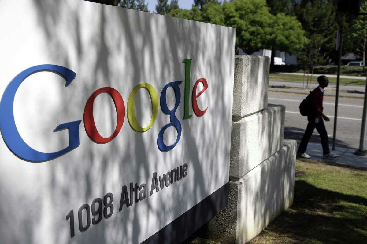 A man walks past a Google sign at the company's headquarters in Mountain View, Calif.