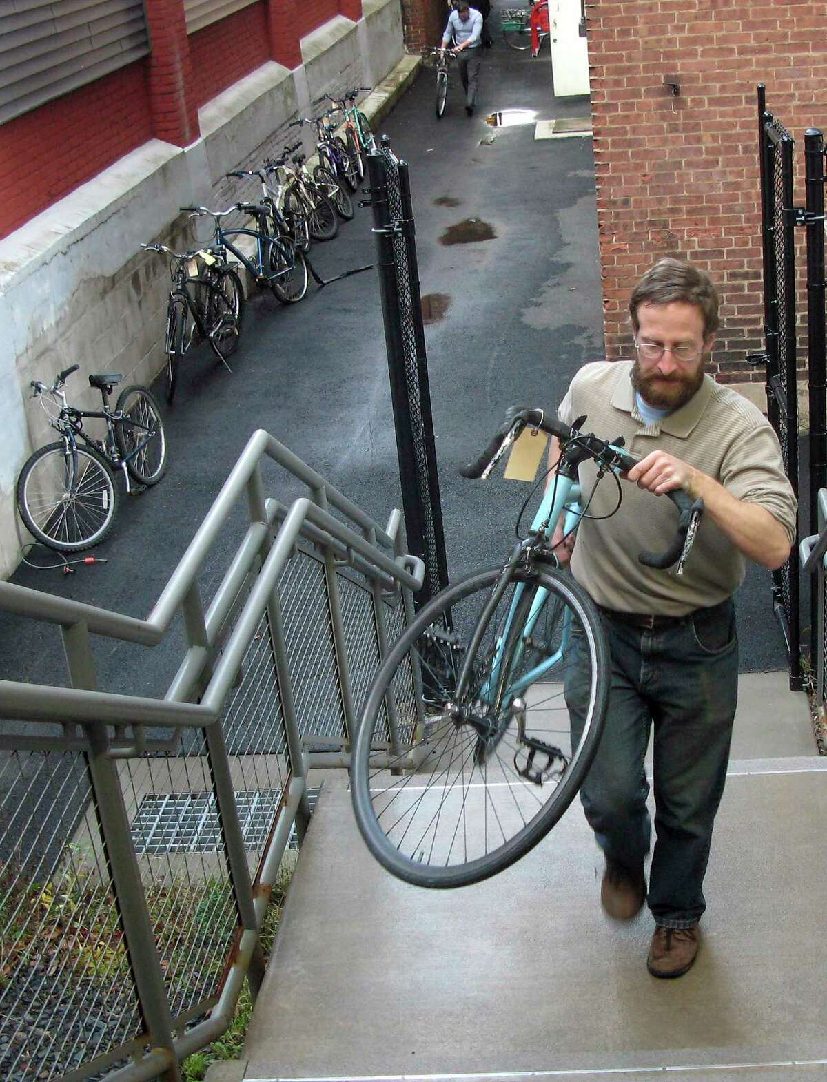 Tony Cherolis, a youth specialist with the Center for Latino Progress in Hartford, unloads bicycles donated by the University of Connecticut.