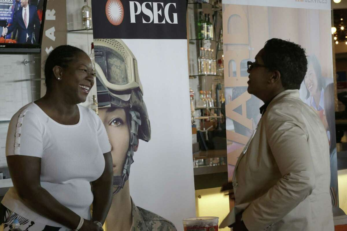 Sophia Lewis, left, with PSEG Long Island, speaks to an attendee about employment opportunities during a job fair June 30 at Citi Field in New York.