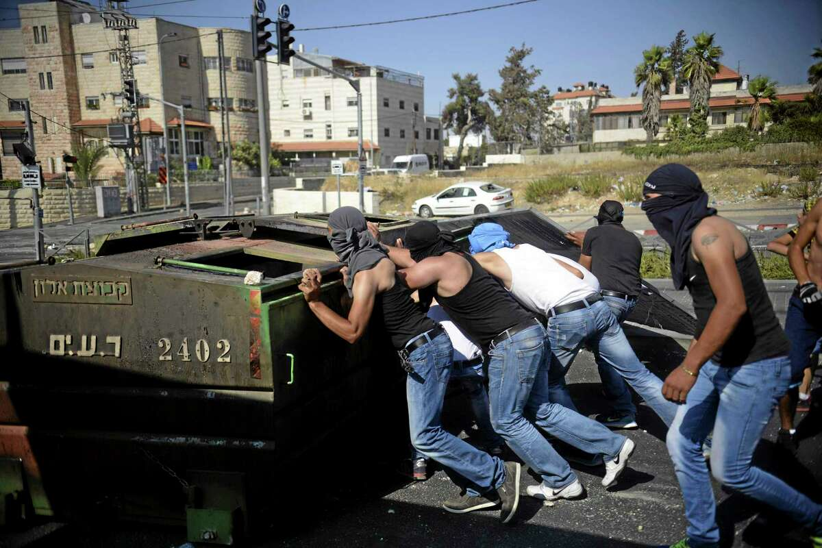 Palestinians push a garbage container as they clash with Israeli security forces during the funeral of 16-year-old Mohammed Abu Khdeir in Jerusalem on Friday, July 4, 2014. Israeli police clashed with Palestinian protesters in Jerusalem on Friday as thousands of people converged on a cemetery for the burial of an Arab teenager, who Palestinians say was killed by Israeli extremists in a suspected revenge attack. (AP Photo/Mahmoud Illean)