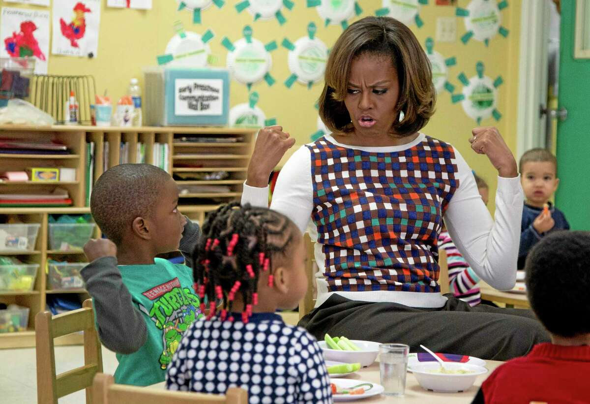 FILE - In this Feb. 27, 2014 file photo first lady Michelle Obama and a young student show off their muscles as they eat healthy snacks during a visit to La Petite Academy in Bowie, Md., to encourage healthy habits at preschool as part of her Let's Move! Child Care program. First ladies typically avoid getting into public scraps, but Obama is in the biggest fight of her tenure as she pushes back against a House Republican effort to soften a key component of the anti-childhood obesity effort at the center of her legacy. And she says she is ready ìto fight until the bitter end,î if that is what it takes. (AP Photo/Carolyn Kaster, File)