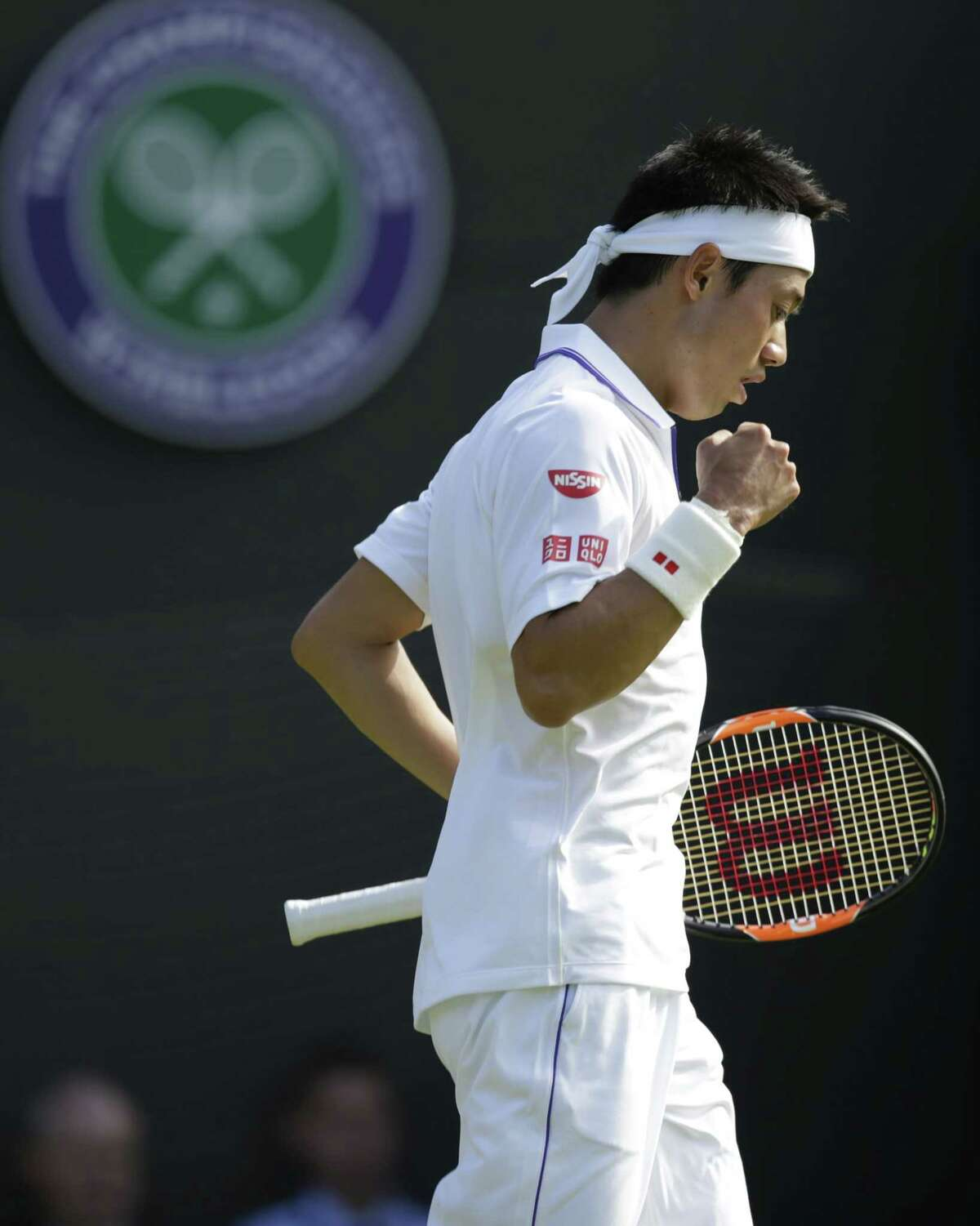 Kei Nishikori of Japan celebrates winning the third set against Simone Bolelli of Italy during the men's singles first round match at the All England Lawn Tennis Championships in Wimbledon, London on June 29, 2015.