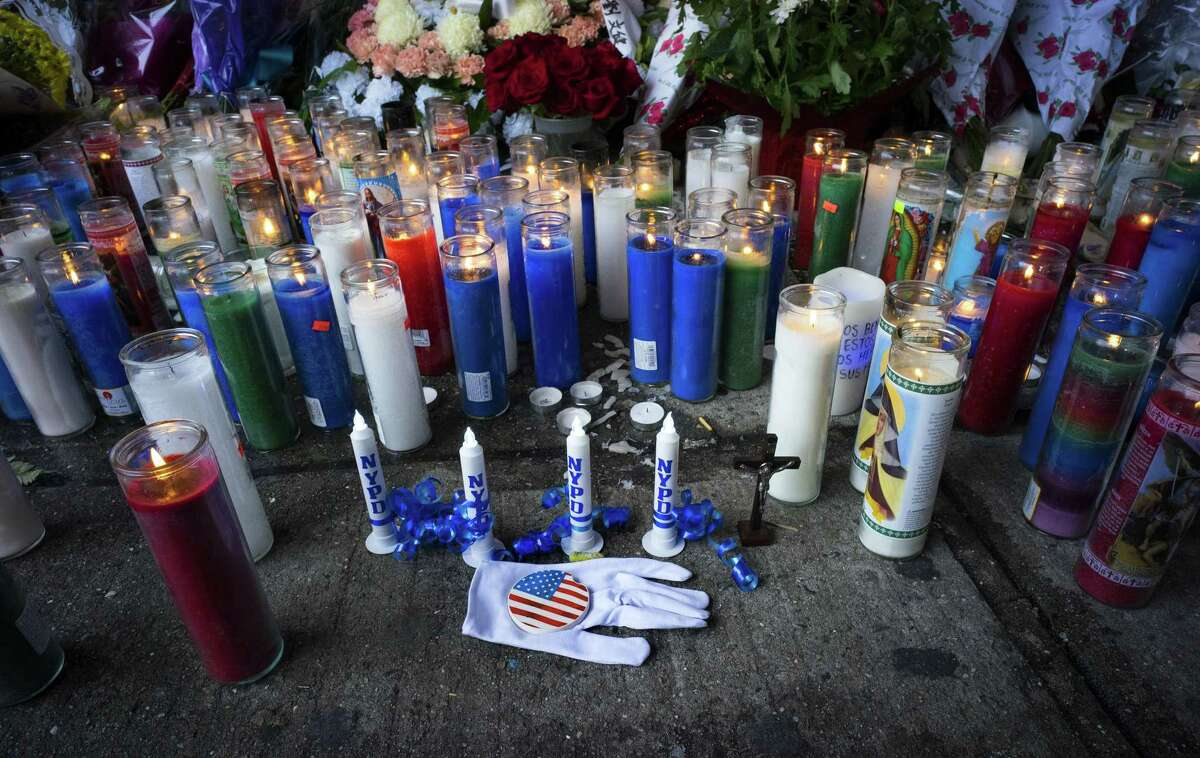 Candles and other items left by visitors make up a growing makeshift memorial Tuesday near the site where New York Police Department officers Rafael Ramos and Wenjian Liu were killed in the Brooklyn borough of New York.