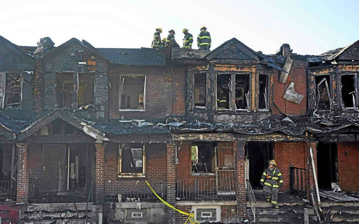 Philadelphia firefighters work on burned row homes on Saturday, July 5, 2014, in Philadelphia. Authorities say the fast-moving fire early Saturday has killed four children. Fire department officials say there is no immediate word on how many others were injured in the blaze that destroyed eight homes in the row and engulfed a total of 10 houses. (AP Photo/Michael Perez)