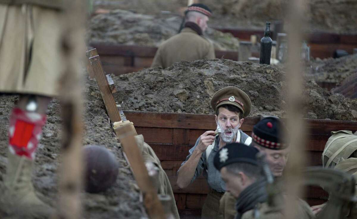 A man prepares to shave as re-enactors, from various living history groups, dressed in World War I British uniforms wait in their trenches during a re-enactment of the 1914 Christmas Truce in Ploegsteert, Belgium on Dec. 20. During that first Christmas Day in World War I, something magical happened. Soldiers who had been killing each other by the tens of thousands for months climbed out of their muddy trenches to seek a shred of humanity amid the horrors of war. Hands reached out across the narrow divide, presents were exchanged, and in Flanders Fields a century ago, a spontaneous Christmas truce briefly lifted the human spirit.