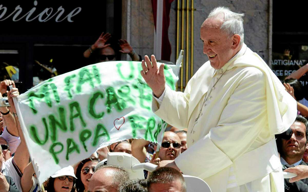"""Faithful hold up a banner reading in Italian, """"Can you caress me Pope Francis"""" as the pontiff arrives Saturday at Campobasso Cathedral in Italy."""