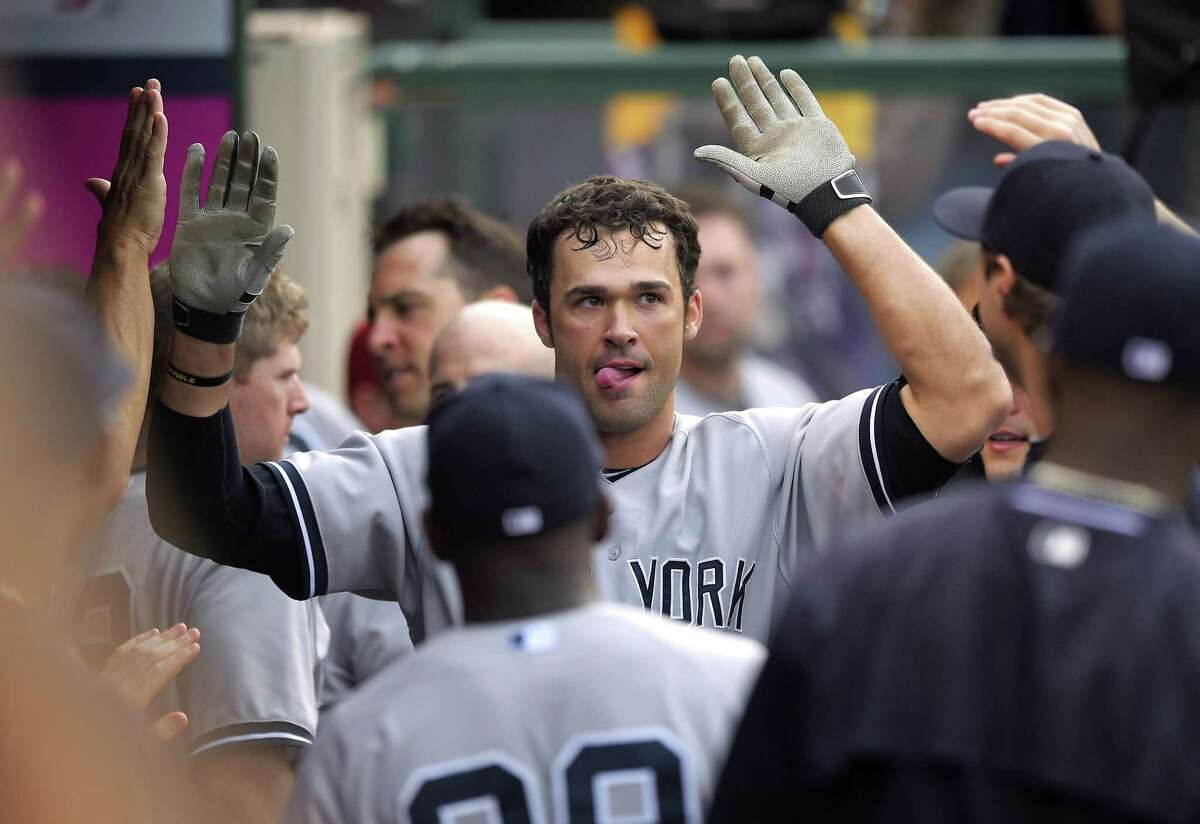 Yankees' Garrett Jones is congratulated by teammates after hitting a solo home run during the sixth inning.