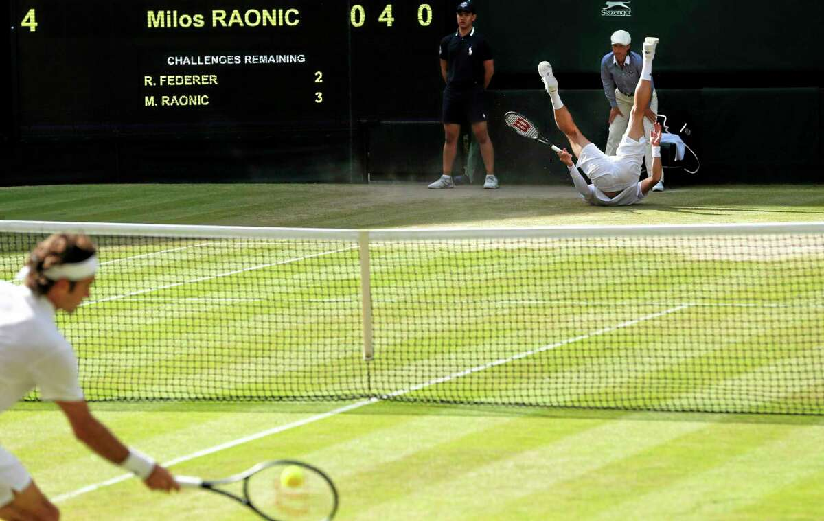 Milos Raonic falls over as Roger Federer plays a return during their semifinal match Friday at the All England Lawn Tennis Championships in Wimbledon, London.