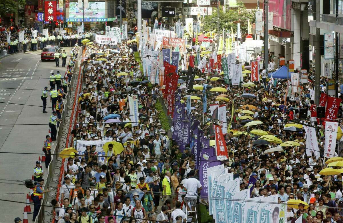 Pro-democracy protesters march during an annual protest marking Hong Kong's handover from British to Chinese rule in 1997 in Hong Kong, Wednesday, July 1, 2015. Thousands of Hong Kongers in crowds noticeably smaller than previous years took to the streets Wednesday to renew their call for full democracy for the Asian financial hub in a rally that follows a turbulent year of protests over political reform. (AP Photo/Kin Cheung)