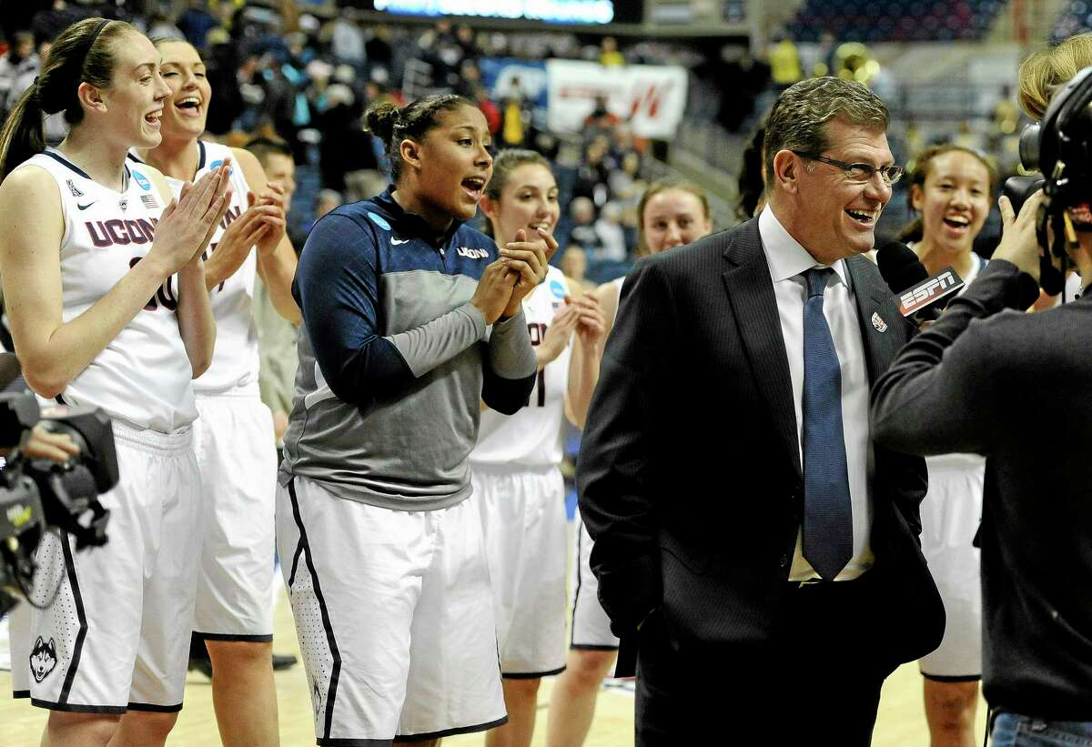 """The Huskies sing """"Happy Birthday"""" behind head coach Geno Auriemma as he is interviewed on live television after UConn's 87-44 win over Prairie View A&M in a first-round game of the NCAA tournament on Sunday night in Storrs. Auriemma turned 60 on Sunday."""