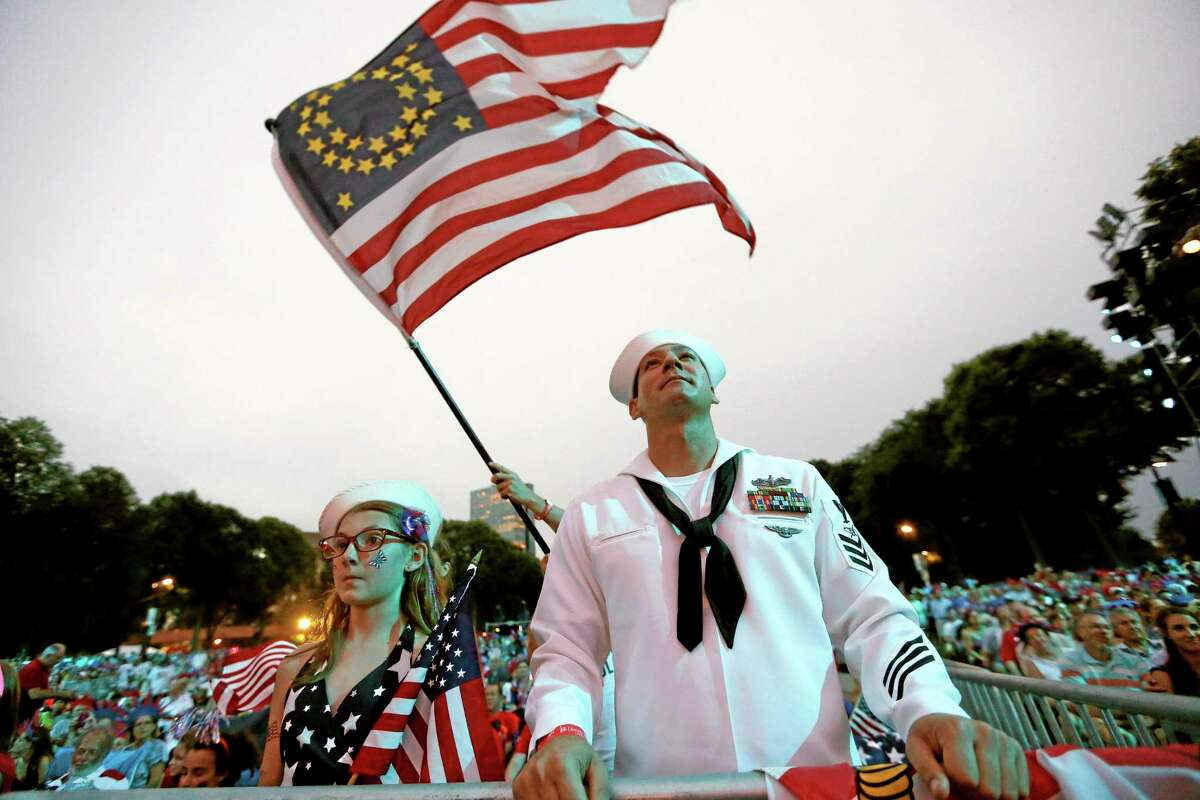 Petty Officer 1st Class Jason Thompson, right, of Detroit, and Megan Schinker, 13, of Stow, Ohio, watch a reading by Massachusetts Gov. Deval Patrick during a concert at the Hatch Shell on the Esplanade in Boston, Thursday, July 3, 2014. The annual Boston Pops Fourth of July concert was moved up a day because of potential heavy rain ahead of Hurricane Arthur. (AP Photo/Michael Dwyer)