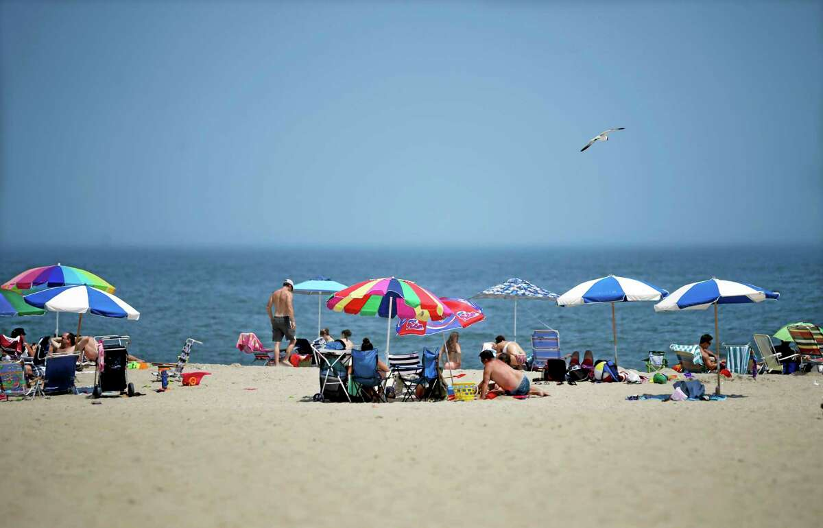 Early arrivals relax on the beach Thursday, July 3, 2014, in Point Pleasant Beach, N.J., at the start of the July 4th weekend. (AP Photo/Mel Evans)