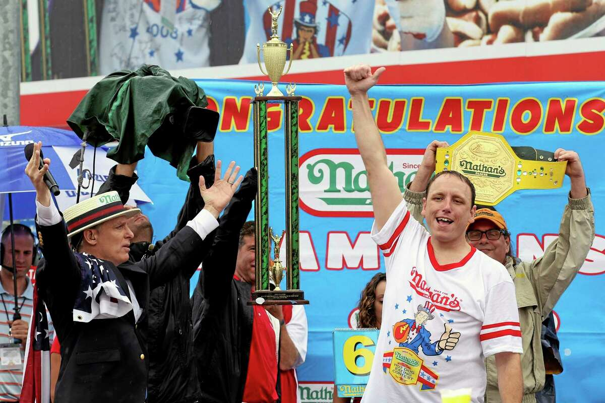 Joey Chestnut raises his fist in the air after winning Nathan's Famous Fourth of July International Hot Dog Eating contest at Coney Island, Friday, July 4, 2014, in New York. Chestnut finished first by consuming 61 hotdogs and buns.
