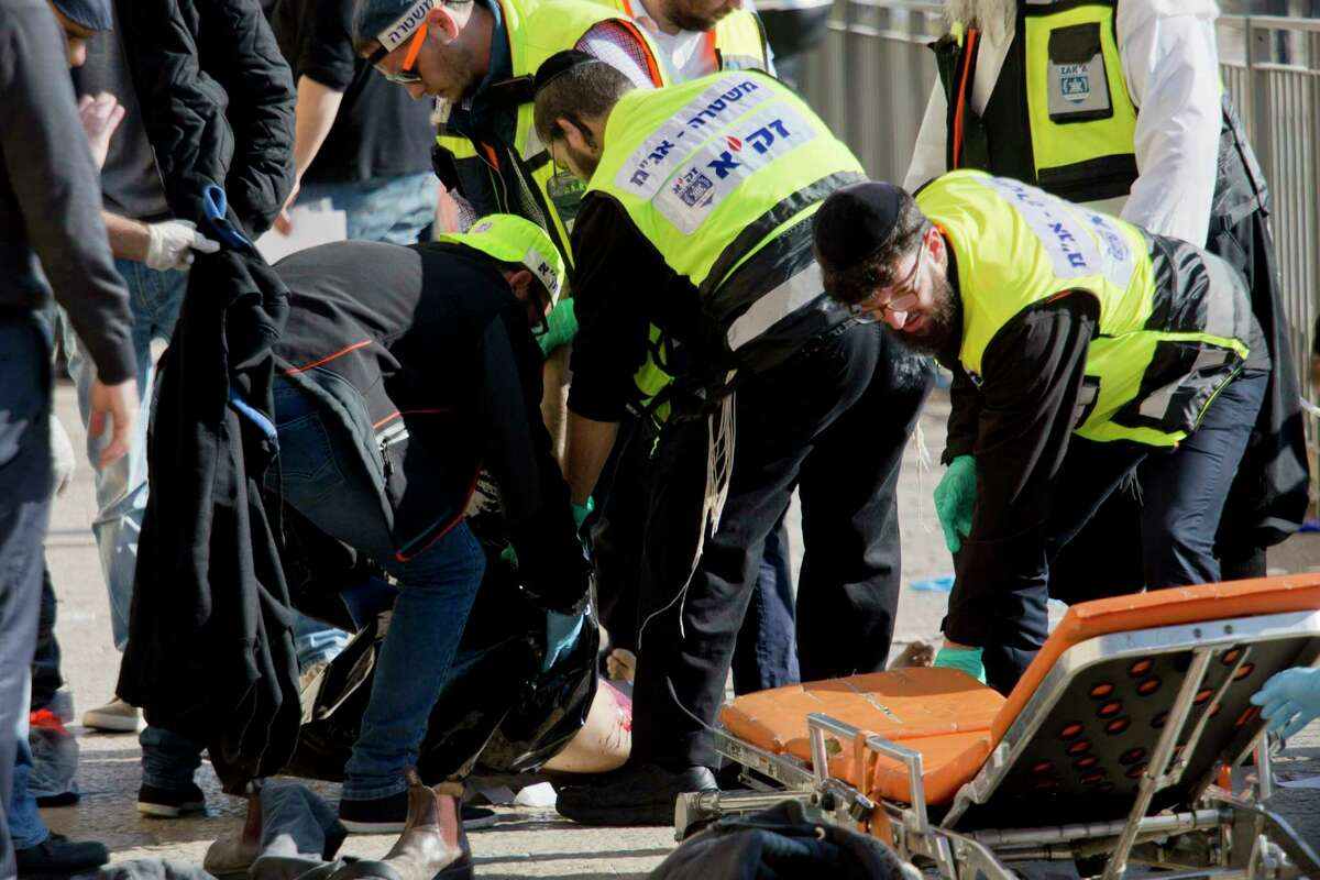 Israeli emergency services officers evacuate the body of a Palestinian assailant form the site outside Jerusalem's Old City, Wednesday, Dec. 23, 2015. Israeli police say one Palestinian assailant was killed and a second was badly wounded after a stabbing attack on Israelis outside Jerusalem's Old City. Police spokeswoman Luba Samri says the two Palestinians attacked Jewish pedestrians outside the city's Jaffa Gate. Samri says police shot both assailants.