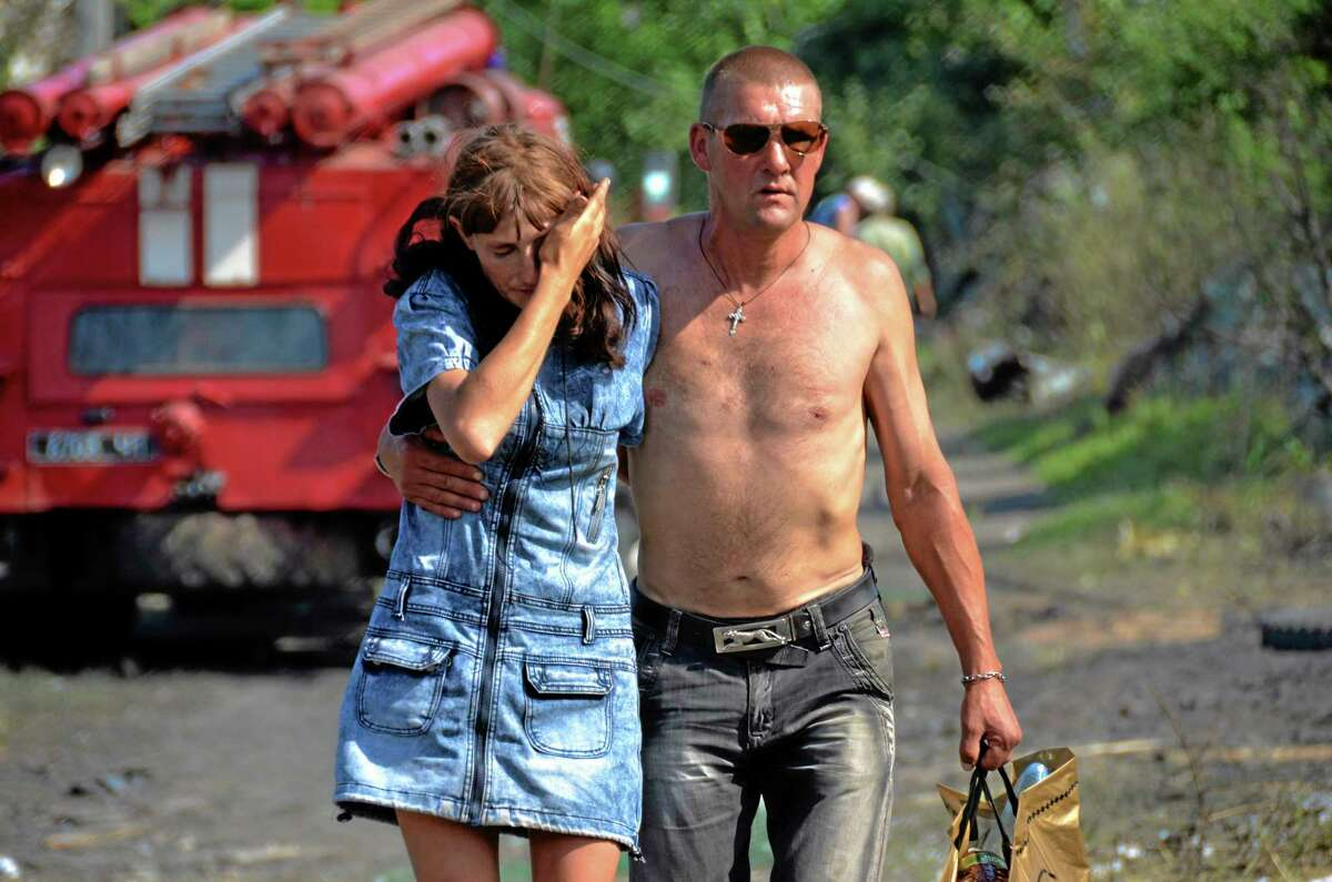In this photo taken on Tuesday, July 2, 2014, Olga, who gave only her first name cries as a local man tries to help her, as they walk together from her burnt house after a Ukrainian Government forces airstrike in Luhanskaya village near Luhansk, eastern Ukraine, (AP Photo, Yuri Snegirev, Rossiyiskaya Gazeta)